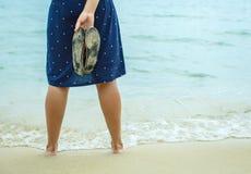 Femme se tenant sur la plage et se tenant dans sa fessée de main Image stock
