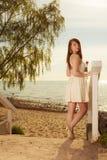 Femme se tenant sur la plage tenant la tulipe rose Image libre de droits