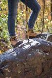 Femme se tenant sur la roche avec augmenter des bottes photographie stock