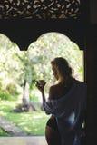 Femme se tenant sur la terrasse avec la tasse Images stock