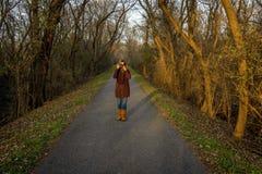 femme se tenant sur la traînée de forêt prenant la photo photographie stock