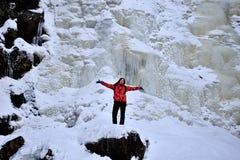 Femme se tenant sur le dessus de la pierre devant la cascade congelée Photographie stock