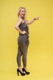 Femme se tenant sur le fond jaune photo stock