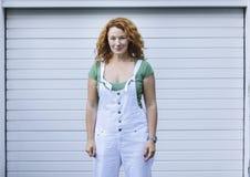 Femme se tenant sur le modèle blanc de minimalisme dans des combinaisons blanches Jour, extérieur Image stock