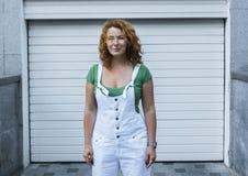 Femme se tenant sur le modèle blanc de minimalisme dans des combinaisons blanches Jour, extérieur Photo stock
