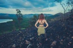 Femme se tenant sur une colline roussie dans un climat tropical Photographie stock