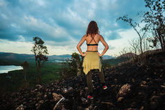 Femme se tenant sur une colline roussie dans un climat tropical Photos stock
