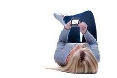 Femme se trouvant dévaluant sur son pda d'isolement Image stock