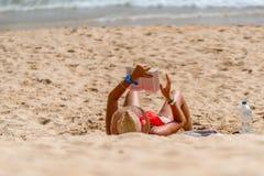 Femme se trouvant sur elle de retour sur une plage lisant un livre Photo stock