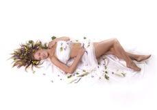 Femme se trouvant sur fleurs Photographie stock