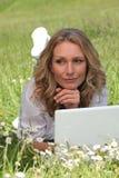 Femme se trouvant sur l'herbe Photographie stock libre de droits