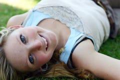 Femme se trouvant sur l'herbe Photo stock
