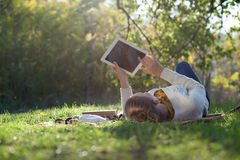 Femme se trouvant sur la literie sur l'herbe verte avec l'ipad Photographie stock
