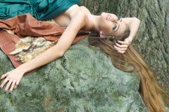 Femme se trouvant sur la pierre Photographie stock