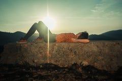 Femme se trouvant sur la roche peu commune au lever de soleil Photographie stock libre de droits
