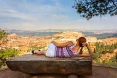 Femme se trouvant sur le banc en haut de la montagne rocheuse Photographie stock