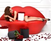 Femme se trouvant sur le divan rouge de sofa de lèvres et la robe rouge avec le bouq de roses image libre de droits