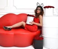 Femme se trouvant sur le divan rouge de sofa de lèvres et la robe rouge avec le bouq de roses Images libres de droits