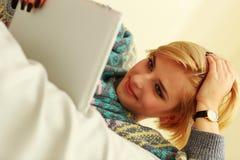 Femme se trouvant sur le lit avec la tablette Photos stock
