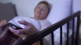 Femme se trouvant sur le lit de malade et les canaux de changement à TV, salle personnelle dans l'hôpital banque de vidéos