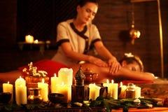 Femme se trouvant sur le lit en bois de station thermale de massage Photographie stock libre de droits