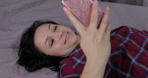 Femme se trouvant sur le lit et ? l'aide du smartphone pour appr?cier la causerie ? l'ami banque de vidéos