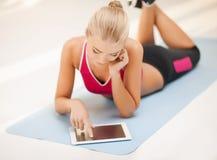 Femme se trouvant sur le plancher avec le PC de comprimé image stock