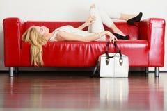 Femme se trouvant sur le sofa présentant le sac blanc images libres de droits