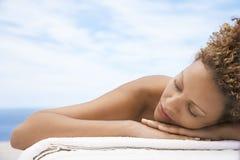 Femme se trouvant sur le Tableau de massage photos stock