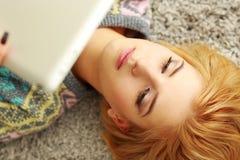 Femme se trouvant sur le tapis avec la tablette Images stock