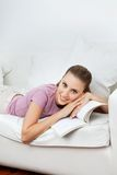Femme se trouvant sur Sofa With Book Photos libres de droits