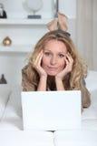 Femme se trouvant sur son estomac Photo stock