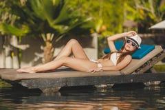 Femme se trouvant sur un canapé à côté de la piscine Image stock