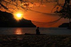 Femme se trouvant sur un hamac par la plage au coucher du soleil et au ciel rouge image stock