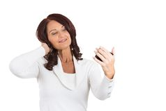 Femme semblant admirative son visage, cheveux dans le miroir images stock