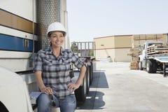 Femme semblant partie tout en se tenant prêt le camion à plat dans la cour de bois de construction Image libre de droits