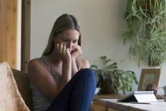 Femme semblant soumise à une contrainte avec la technologie Photographie stock