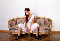 Femme sensuel s'asseyant sur le sofa photo stock