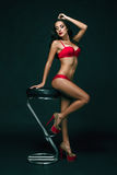 Femme sensuelle de brune avec le corps parfait posant dans la lingerie, tenant la rose de rouge Images stock