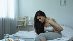 Femme sentant la crampe pointue de douleur forte, problèmes avec les organes pelviens, cystite clips vidéos
