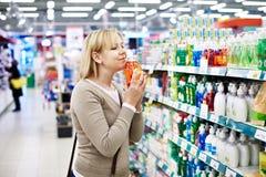 Femme sentant le savon liquide parfumé dans le magasin photo stock