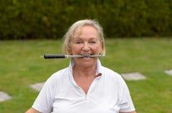 Femme sereine supérieure mordant sur un dossier Photos stock