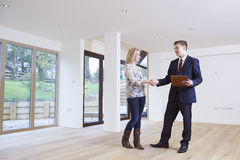 Femme serrant la main à l'agent immobilier In New Home photos stock
