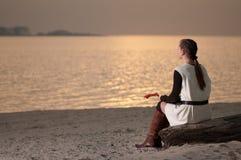 Femme seul s'asseyant sur la côte de lac photos libres de droits
