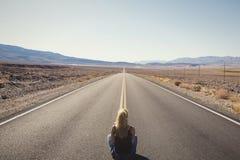 Femme seul s'asseyant sur la rue au milieu de nulle part Concept d'envie de voyager photographie stock libre de droits