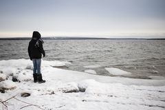 Femme seul se tenant sur un rivage de lac couvert par neige par temps froid d'hiver photographie stock libre de droits
