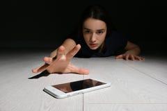 Femme seule atteignant pour le téléphone intelligent sur le plancher à l'intérieur images stock