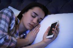 Femme seule dormant avec le téléphone intelligent images stock