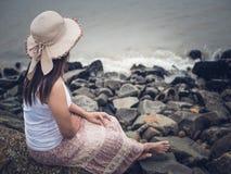 Femme seule et déprimée s'asseyant devant la mer Images stock