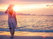 Femme seule et déprimée tenant un chapeau et une position devant la mer Photos stock